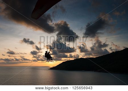 Paraglider flying at the sunset time at the shore of Phuket Thailand