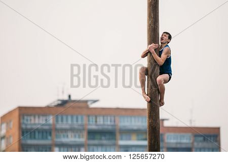 GOMEL, BELARUS - February 21, 2014: Young man climbs on a wooden post on the traditional holiday dedicated to the approach of spring - Slavic celebration Shrovetide.