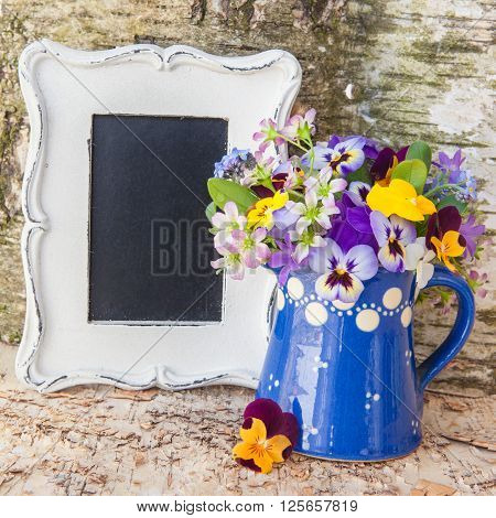 Little bouquet of spring flowers in blue ceramic can