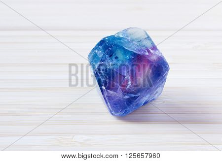 Multi colored fluorite fluorspar mineral crystal on wooden table. Photo of this sample can be used for geology science.