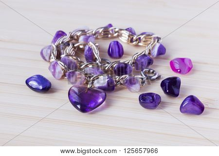 Cute lilac natural amethyst beads stones crystals and old vintage bracelet with amethyst heart on bamboo wooden table.