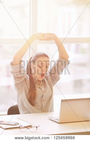 Young exhausted depressed concentrated woman sitting in her room or office with french windows and studing. Overworking.