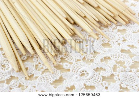 Various bamboo wooden knitting needles on crochet background.