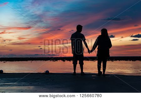 Silhouette of couple hold each other hand on the beach at sunset time