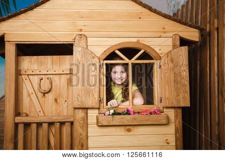 Little girl inside wooden house. Stock photo.