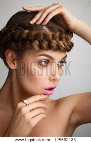 Portrait Of A Young Lady With A Braid On Grey Background