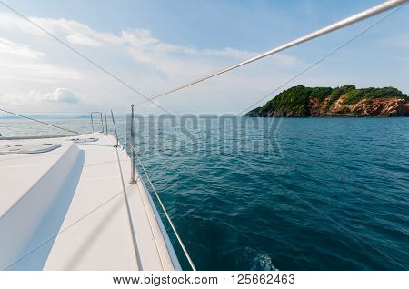 Private catamaran boat sailing to the island ahead. Luxury Lifestyle. Traveling on a yacht