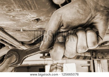 Dirty hand is holding wrench. Car servis.