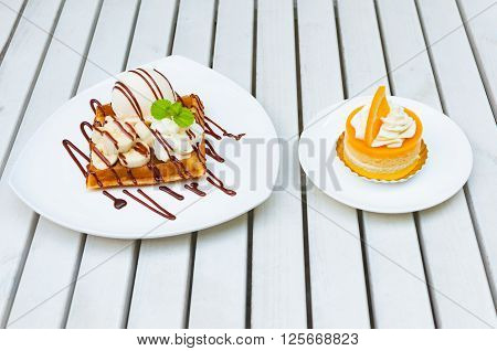 Ice cream waffle banana with chocolate sauce and orange layer cake serve on white plates over the white wooden table