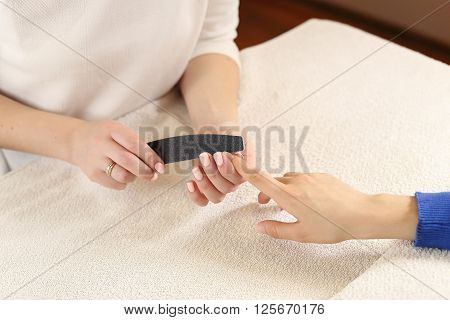 Filing nails process in spa salon, close up view