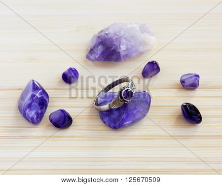 Multi color gems stones minerals and the old vintage silver ring on wooden table. Colorful background with amethyst gems.