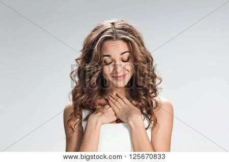 The modest woman is looking imploring  over gray background