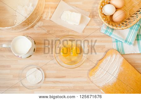 Ingridients for bread baking on light wooden background. Cutting board eggs salt flour raw eggs milk butter towel sieve.