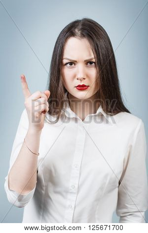 Young angry woman threaten finger on the gray background
