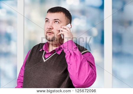 Handsome businessman with crossed hands standing on the blured window background