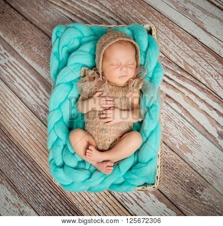 cute newborn baby in costume on turquoise blanket in cot top view