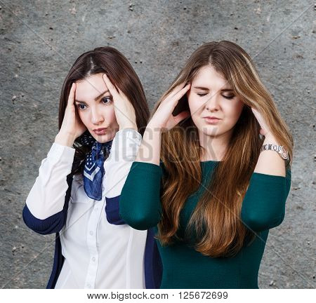 Two women with a headache on the gray wall background
