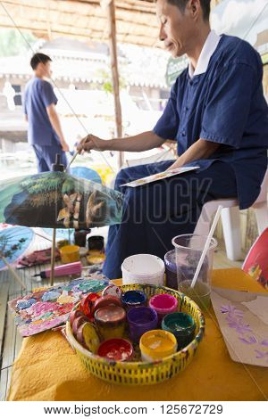 The Artisan Painting Picture On Traditional Thailand Lanna Paper Umbrella