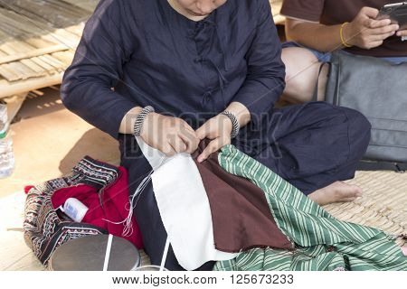 Chiang Mai Thailand - April 13 2016: The woman sewing traditional Thai fabric textile at the ancient lanna house 140 years in water festival in Chiang Mai Thailand on April 13 2016.
