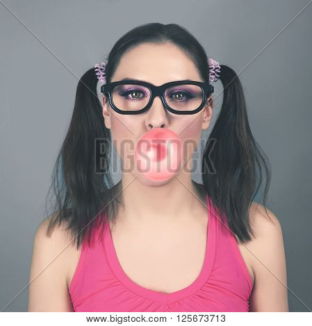 Beautiful young fashion funny model girl wearing hipster glasses with bubble of chewing gum