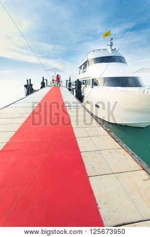 Yacht docking at the pier with red carpet to party on board