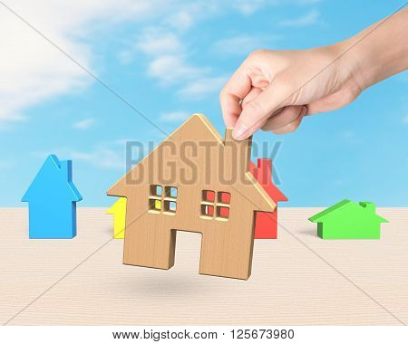 Woman hand picking wooden house with colorful small houses on wood table and sky background.