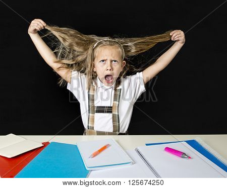 crazy cute junior schoolgirl sitting on desk in stress working doing homework pulling her blond hair crazy and overwhelmed in children education and school hard work