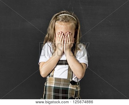 young sweet junior schoolgirl with blonde hair crying sad and shy standing isolated in front of school class blackboard wearing school uniform in children education stress