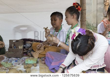 CHIANG MAI, THAILAND - APRIL 13: boy and girl molding clay figurine at the ancient lanna house 140 years in water festival in Chiang Mai Thailand on April 13 2016.