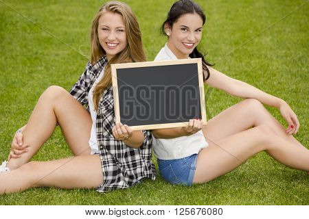 Tennage students sitting on the grass and holding a chalkboard
