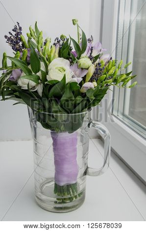Beautiful spring bouquet of wedding flowers buttercup ranunculus fresia lavender in vase with violet tape. Pastel colors purple green. Rustic style still life. Holiday wedding floristic bouquet of bride. Marriage. White Background.