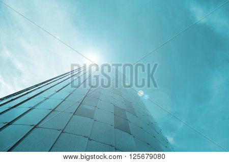 Low view image. Modern glass building skyscrapers over blue bright clear sky with sunlight. Copy space for Publisher's text.