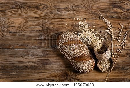 Top view of bread with rolled oats and oat florets on old wooden background with space.
