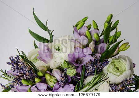 Beautiful spring bouquet of wedding flowers white violet green buttercup ranunculus fresia. Background soft macro. Rustic style still life. Holiday wedding floristic bouquet of bride. Marriage.