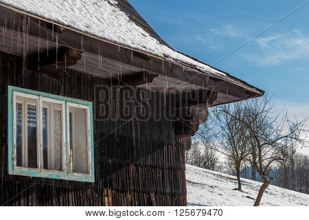 Detail on old winter chalet in Czech Republic with snow melting and water drops falling from the roof