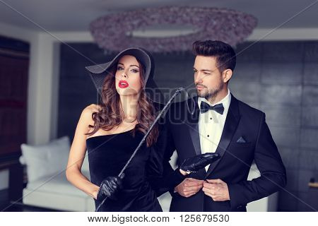 Sexy dominatrix woman posing with whip and young macho lover in tux
