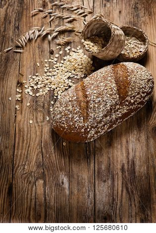 Oat bread with oat flakes and oat florets on old wooden background with copy space.