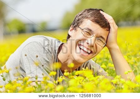 Portrait of young hispanic man wearing glasses, lying down on meadow in spring park outdoors with hand on his head, smiling perfect healthy toothy smile - humor, dentistry or ophthalmology concept