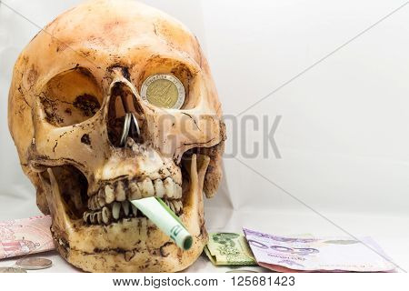 Skull fragment with a little money on a white background, focus on the eye.