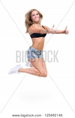Young sexy woman in jeans shorts jumping with thumbsup, isolated on white background in full length.