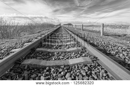 Long straight railroad from rusty rails on concrete sleepers in a rural area in the Netherlands.
