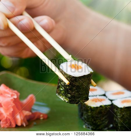 Man's hand holding sushi with chopsticks, Japanese seafood