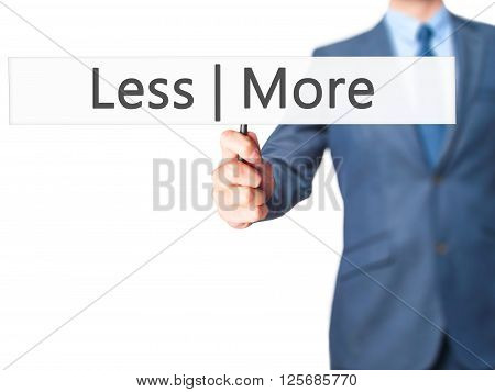 Less  More - Businessman Hand Holding Sign