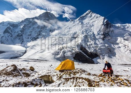 High Snowbound Peaks and Man Packing his Climbing Backpack Staying next to Orange Tent