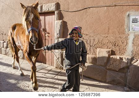 PISAC, PERU- SEPTEMBER 25, 2015: Smiling boy walks with his horse in a typical street in Pisac, Peru