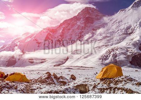 Steep Snowbound Peaks Bivouac Assembled on Rocky Moraine of Glacier Sun Shining
