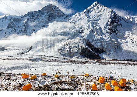 Many Orange Tents Located on Side Rock Moraine of Glacier in Severe Snow and Ice Peaks Landscape