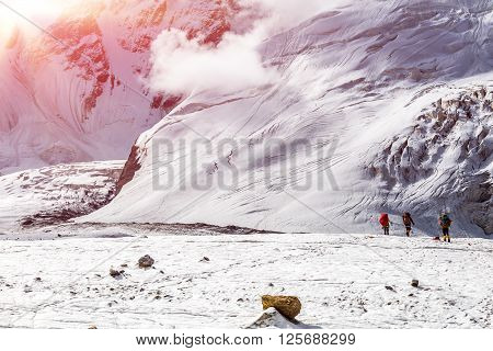 Massive Glacier at High Altitude Severe Mountains and Small Body of Alpine Climber with Backpack and Trekking Poles Walking on Ice  Clouds Moving Down