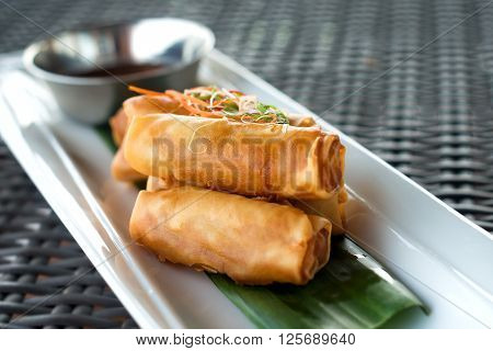 Vegetable fried spring rolls served with bittersweet sauce on wicker table close up.