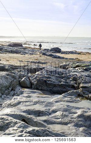 lone man walking on the rocks at ballybunion beach in ireland